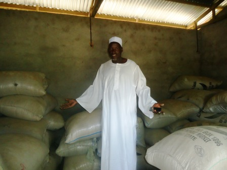 un délégué de Gic à Maga dans un magasin avec des sacs de sorgho