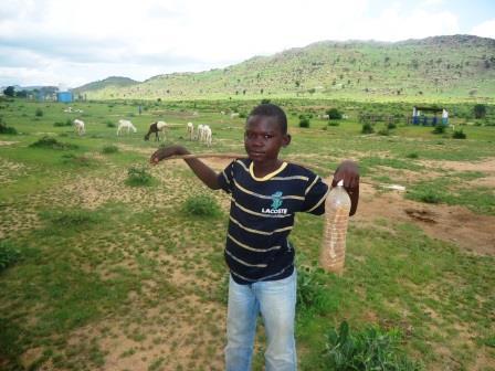 Un petit garçon qui tient le bâton de commandement de son troupeau. des chèvres en arrière plan.