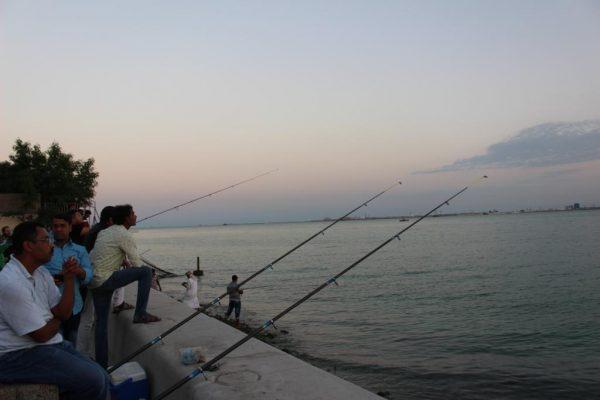 Des hommes en train de pêcher avec leur hameçons.